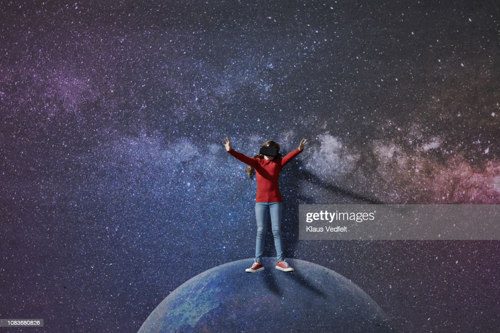 Girl wearing VR goggles standing on imaginary painted planet in space : Stock Photo