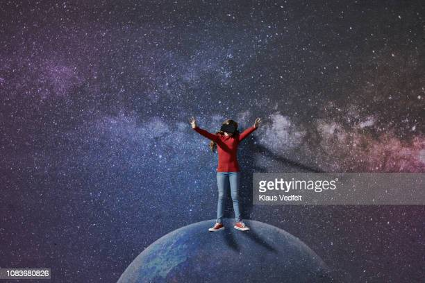 Girl wearing VR goggles standing on imaginary painted planet in space