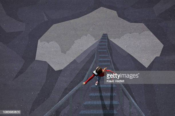 Girl wearing VR goggles standing on staircase path in a cave scenery