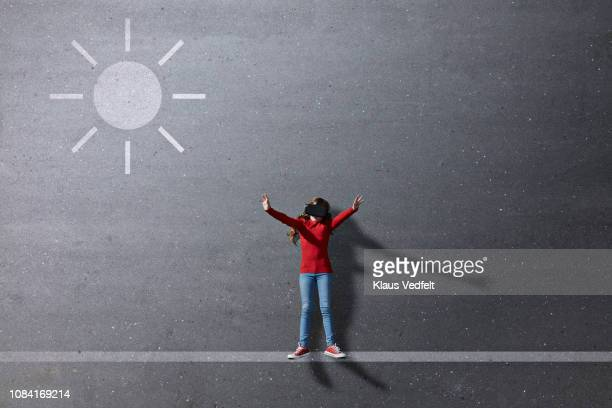 Girl wearing VR goggles standing under imaginary painted sun