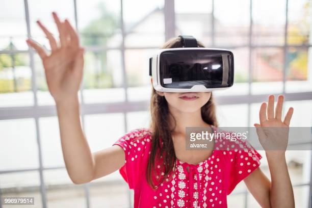 Girl wearing VR headset while gesturing in class