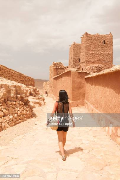 Girl wearing walks next to a wall in a fortified construction