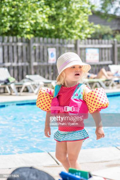 girl wearing water wings while walking on poolside during sunny day - armband stock pictures, royalty-free photos & images