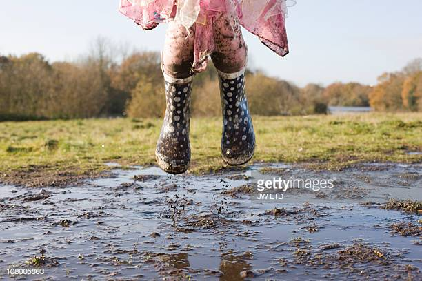 girl wearing wellington boots jumping in muddy puddle - opstand stockfoto's en -beelden