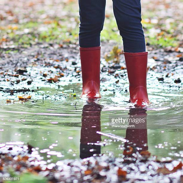 Girl wearing wellington boots standing in puddle