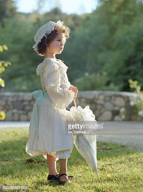 girl (3-5) wearing white dress, holding umbrella - petite fille culotte photos et images de collection