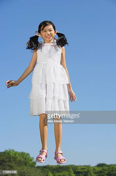 Girl wearing white dress, jumping in mid air, smiling at camera