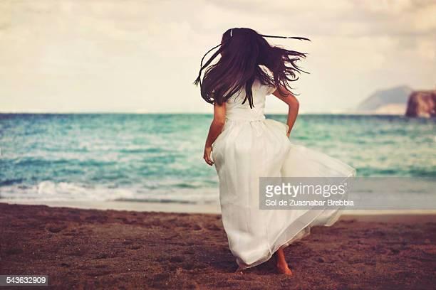 Girl wearing white dress running at the beach