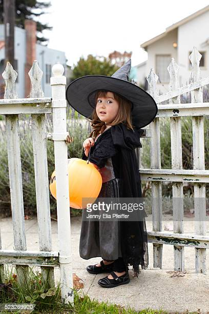 Girl (2-3) wearing witch costume holding pumpkin
