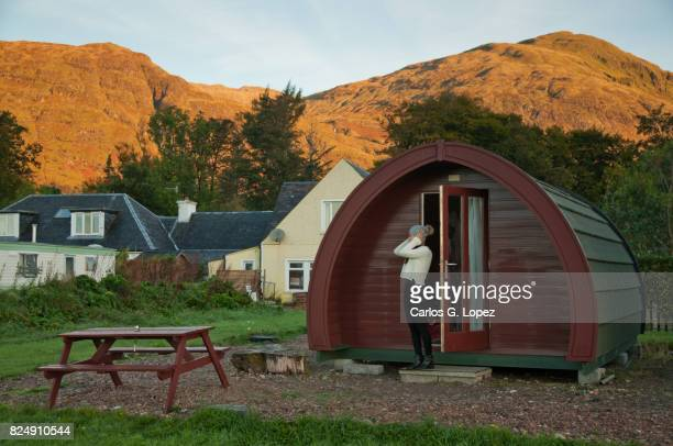 Girl wearing wooly hat stands ourside a cabin pod in the highlands