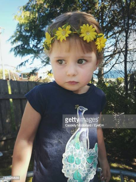 Girl Wearing Yellow Flowers On Hair Against Tree