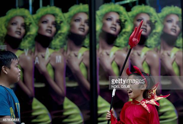 A girl wears a devil costume as she attends the Cats and Dogs Halloween costume competition in Manila on October 25 2014 The annual halloween event...