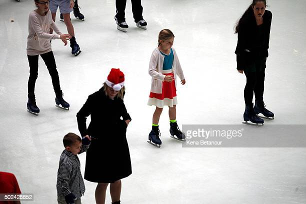A girl wears a dress while ice skating at the rink at Rockefeller Center on December 24 2015 in New York City New York City has seen highs in the...