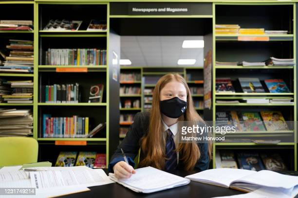 Girl wears a face mask while at work in the library at Willows High School on March 16, 2021 in Cardiff, Wales. Secondary schools in Wales reopen...