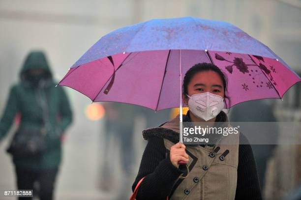 A girl wears a face mask while walking past a building shrouded in severe air pollution on November 7 2017 in Harbin China Meteorological authorities...