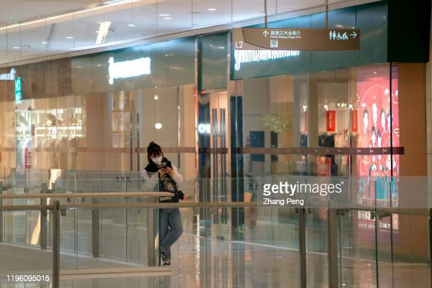 A girl wears a mask in an empty shopping mall Wuhan New coronavirus pneumonia has been spread around all provinces in China but Tibet The government...