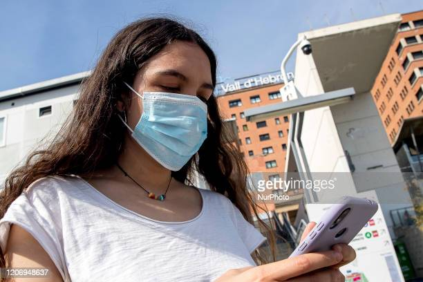 A girl wears a medical mask in front of Vall d'Hebron Hospital during the COVID19 crisis in Barcelona Catalonia Spain on March 12 2020
