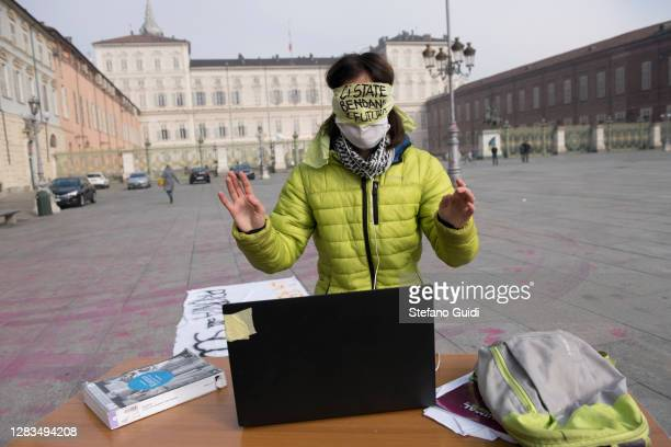 Girl wears a protective mask behind a school desk during a student protest in Piazza Castello in front of the Piedmont Region building on November...