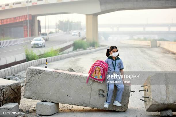 A girl wears pollution mask as she waits for her school bus on a smoggy morning at Mayur Vihar on October 24 2019 in New Delhi India