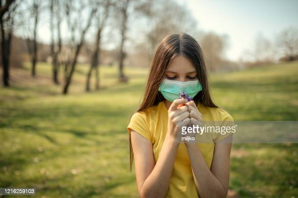 girl wears protective mask outdoors and smelling flowers - miljko stock pictures, royalty-free photos & images