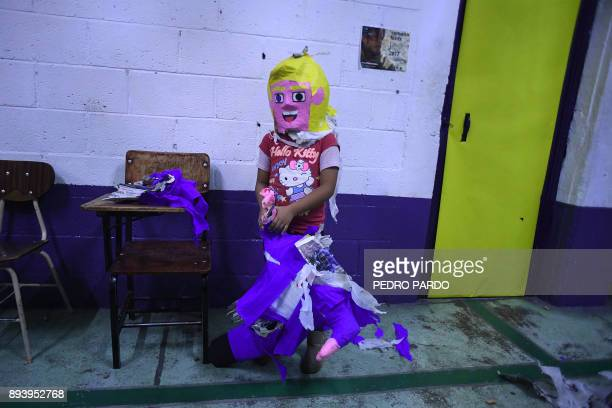 A girl wears the head of a pinata with the figure of US President Donald Trump during a traditional posada in Mexico City on December 16 2017 The...