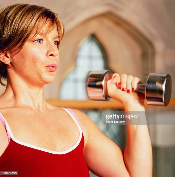 Girl weight lifting with dumbbell in gym