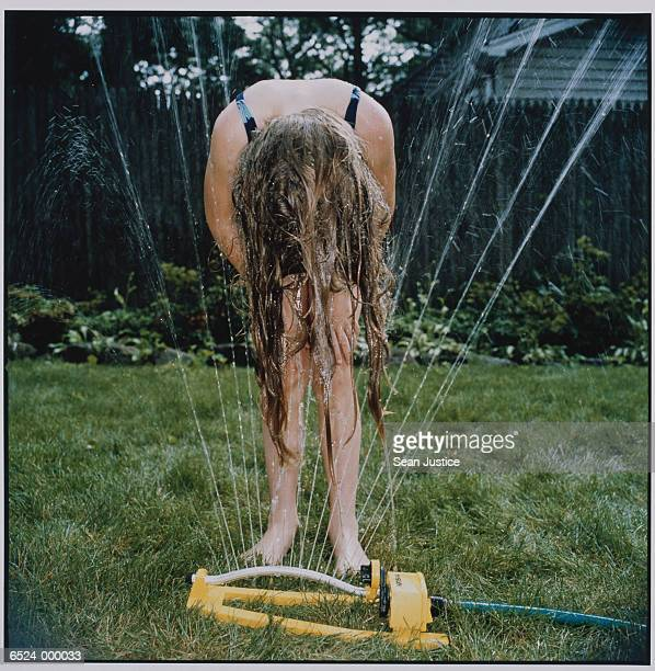 girl wetting hair in sprinkler - little girls bent over stock photos and pictures