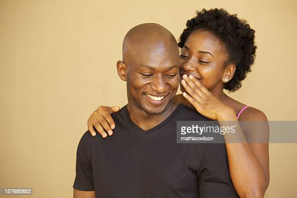 Girl whispering in a guy's ear