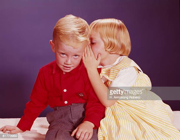 Girl whispering in ear of boy. (Photo by H. Armstrong Roberts/Retrofile/Getty Images)