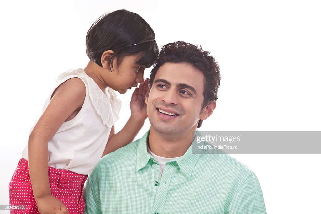 Girl whispering in fathers ear : Stock Photo