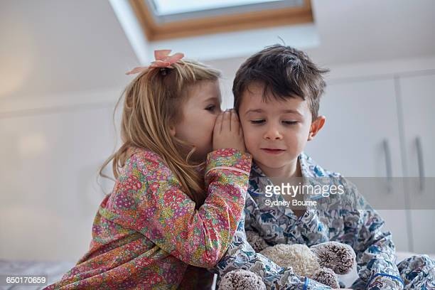 Girl whispering into boys ear in loft room