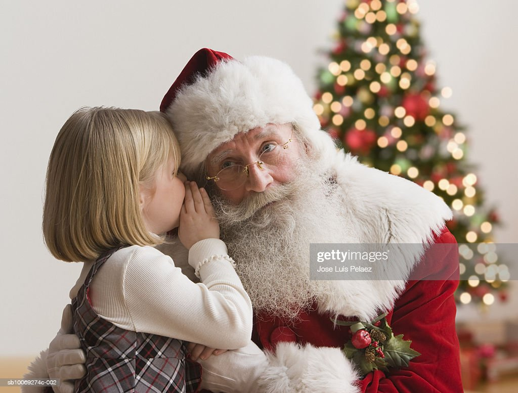 Girl (4-5) whispering into Santa's ear, close-up : Stockfoto