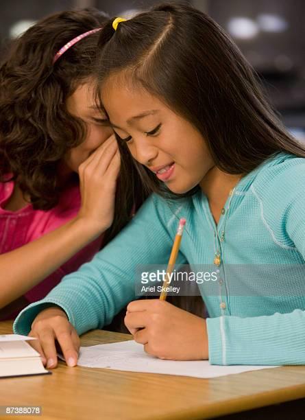 girl whispering secret to friend in classroom - ariel rebel fotografías e imágenes de stock