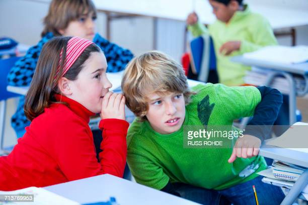 Girl whispering to boy in classroom