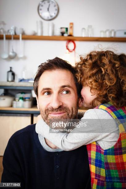 Girl whispering to father in kitchen