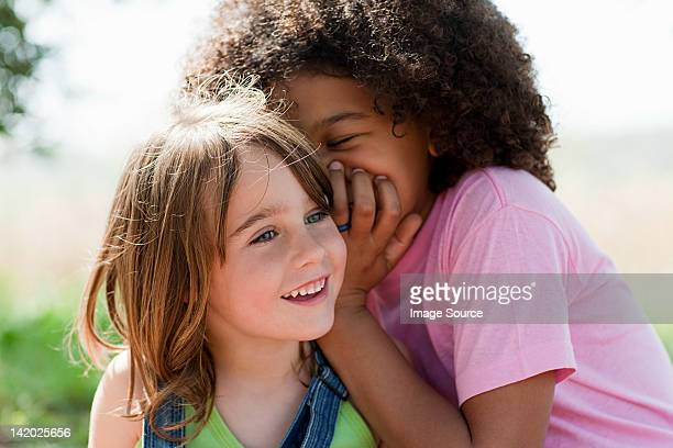 Jeune femme Chuchoter à l'oreille à un (e) ami (e)