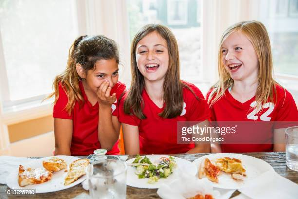 girl whispering to friends at dinner table - soccer uniform stock pictures, royalty-free photos & images