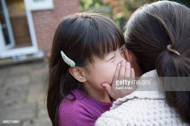 Girl whispering to her mother in the garden