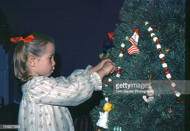 Girl whistling while hanging Christmas ornaments