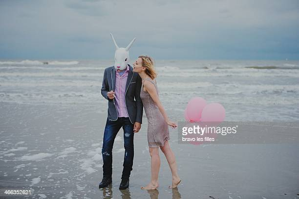 girl, white rabbit and pink balloons at the beach - rabbit beach stock photos and pictures