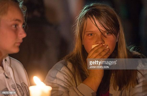 A girl who allegedly had multiple family members involved in a shooting at her college campus reacts during a vigil in Roseburg Oregon on October 1...