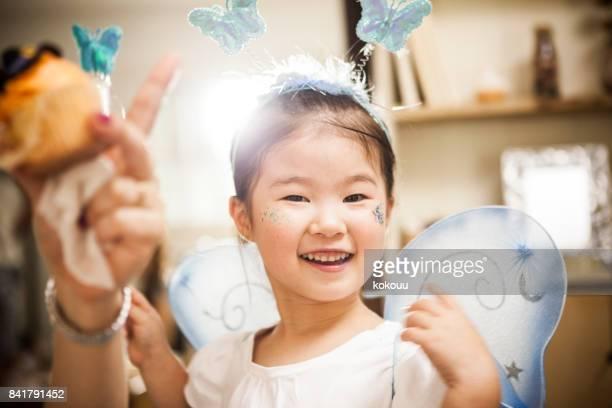 妖精の衣装、女の子は、魔法の杖で遊んでいます。