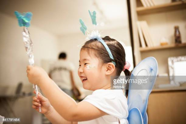 A girl who costumes a fairy is playing with a magic wand.
