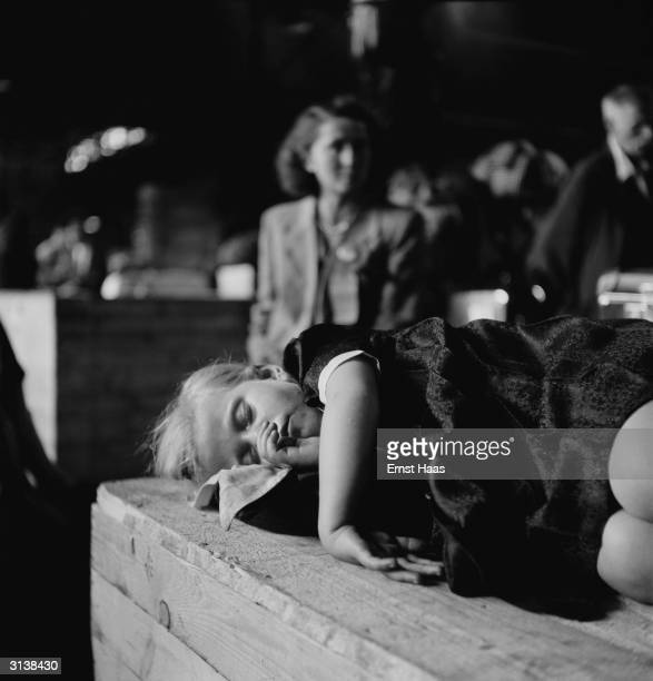 A girl who has just arrived at Ellis Island in New York curls up on a packing case to sleep 1951 She arrived on the USS General R M Blatchford with...