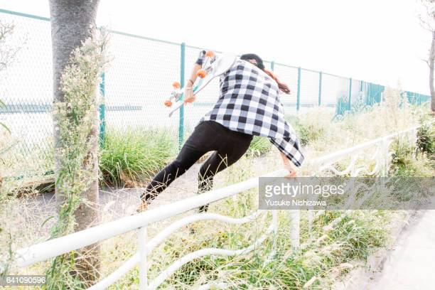 a girl who jumps over the fence - yusuke nishizawa stock pictures, royalty-free photos & images