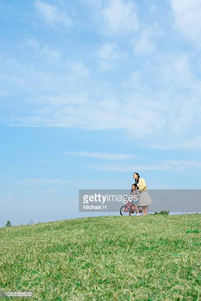Girl who learns how of bicycle to get on