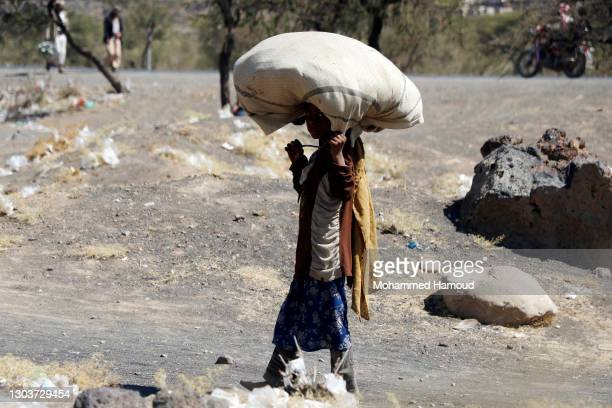 Girl who was displaced due to the ongoing war walks, carrying dried grass to be used in cooking at an internally displaced camp on February 21, 2021...