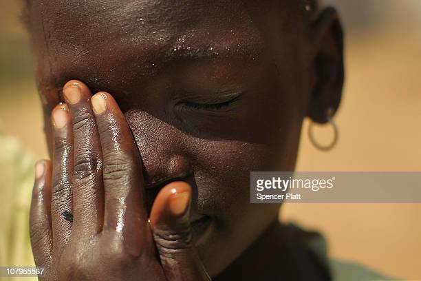 A girl wipes her face while holding a jug of water on her head during the second day of voting for the independence referendum January 10 2011 in...