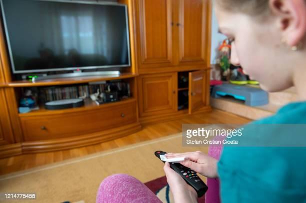 girl wiping down tv remote - cristian neri foto e immagini stock