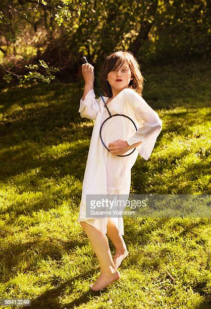 A girl with a badminton bat in the grass Sweden.